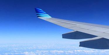 Asa de avião com céu azul e nuvens brancas ao fundo